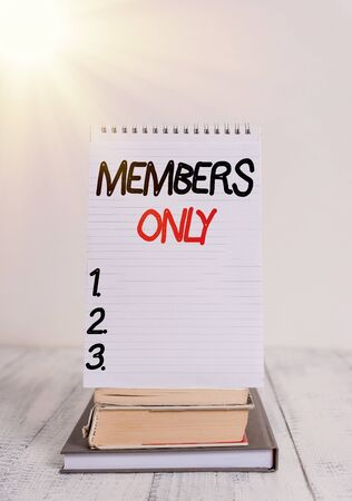 Conceptual hand writing showing Members Only. Concept meaning Limited to an individual belongs to a group or an organization Front view stacked books spiral note book on vintage wooden table