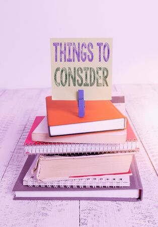 Text sign showing Things To Consider. Business photo text think about something carefully in order to make decision pile stacked books notebook pin clothespin colored reminder white wooden 写真素材