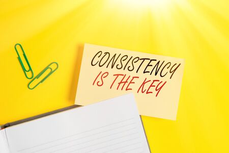 Writing note showing Consistency Is The Key. Business concept for by Breaking Bad Habits and Forming Good Ones Empty orange paper with copy space on the yellow table Foto de archivo
