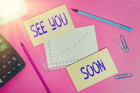 Writing note showing See You Soon. Business concept for used for saying goodbye to someone and going to meet again soon Writing equipments and computer stuffs placed above colored plain table Stock Photo