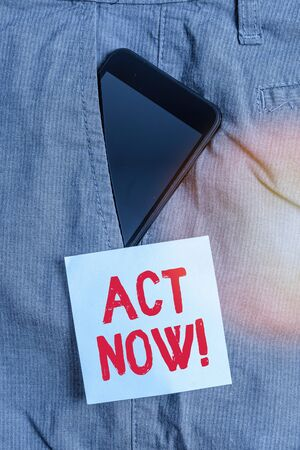 Conceptual hand writing showing Act Now. Concept meaning fulfil the function or serve the purpose of Take action Do something Smartphone device inside trousers front pocket note paper Stock Photo