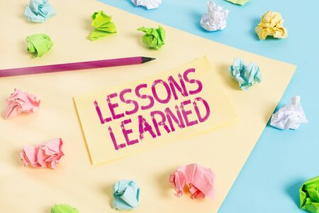 Handwriting text writing Lessons Learned. Conceptual photo the knowledge or understanding gained by experience Colored crumpled papers empty reminder blue yellow background clothespin