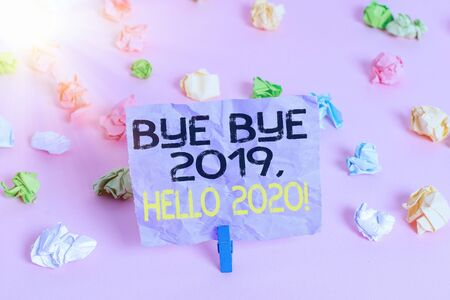 Word writing text Bye Bye 2020 Hello 2020. Business photo showcasing saying goodbye to last year and welcoming another one Colored crumpled papers empty reminder pink floor background clothespin