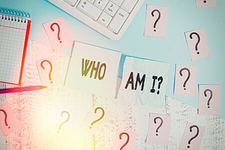 Writing note showing Who Am I Question. Business concept for asking about self identity or personal purpose in life Writing tools and scribbled paper on top of the wooden table Stock Photo