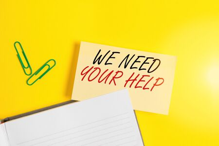 Writing note showing We Need Your Help. Business concept for asking someone to stand with you against difficulty Empty orange paper with copy space on the yellow table