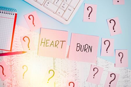 Text sign showing Heart Burn. Business photo showcasing a burning sensation or pain in the throat from acid reflux Writing tools, computer stuff and math book sheet on top of wooden table