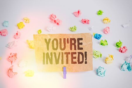 Conceptual hand writing showing You are Invited. Concept meaning make a polite friendly request to someone go somewhere Colored crumpled paper empty reminder white floor clothespin Standard-Bild