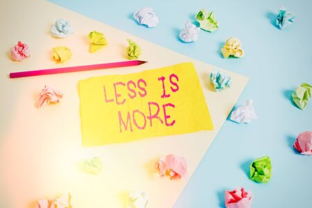 Word writing text Less Is More. Business photo showcasing used to express a minimalist approach is more effective. Colored crumpled papers empty reminder blue yellow background clothespin