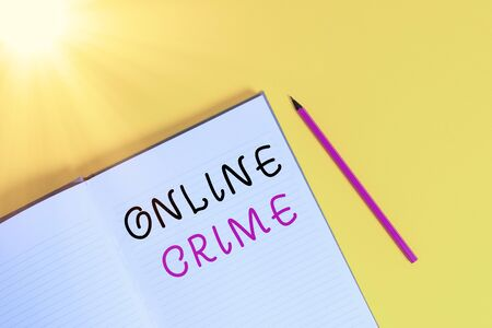 Text sign showing Online Crime. Business photo text crime or illegal online activity committed on the Internet Open striped hard cover notebook lying pencil marker color background