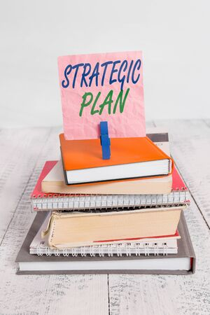 Word writing text Strategic Plan. Business photo showcasing a systematic process of envisioning a desired future pile stacked books notebook pin clothespin colored reminder white wooden