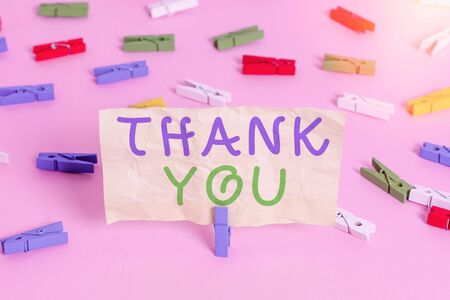Text sign showing Thank You. Business photo showcasing a polite expression used when acknowledging a gift or service Colored clothespin papers empty reminder pink floor background office pin
