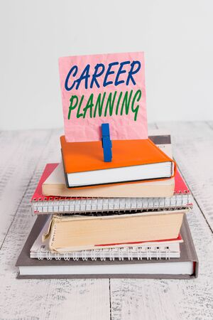 Word writing text Career Planning. Business photo showcasing Strategically plan your career goals and work success pile stacked books notebook pin clothespin colored reminder white wooden