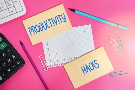 Writing note showing Productivity Hacks. Business concept for tricks that you get more done in the same amount of time Writing equipments and computer stuffs placed above colored plain table