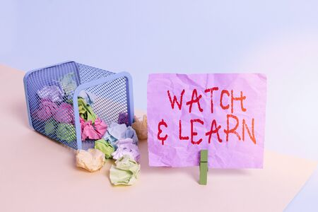 Writing note showing Watch And Learn. Business concept for demonstrating an action or ideas of how to do things Trash bin crumpled paper clothespin reminder office supplies
