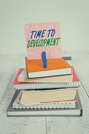 Word writing text Time To Development. Business photo showcasing a length of time during which a company grows or develop pile stacked books notebook pin clothespin colored reminder white wooden Stock Photo