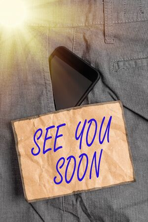 Conceptual hand writing showing See You Soon. Concept meaning used for saying goodbye to someone and going to meet again soon Smartphone device inside trousers front pocket note paper