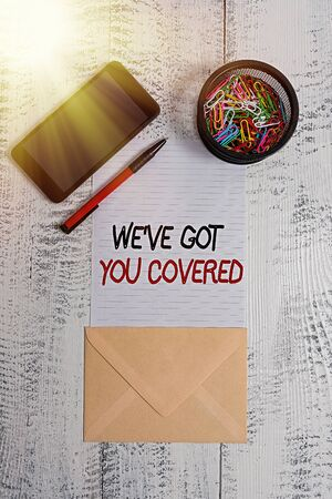 Writing note showing We have Got You Covered. Business concept for have done gotten or provided whatever needed Smartphone paper sheet clips pen envelope wooden vintage background