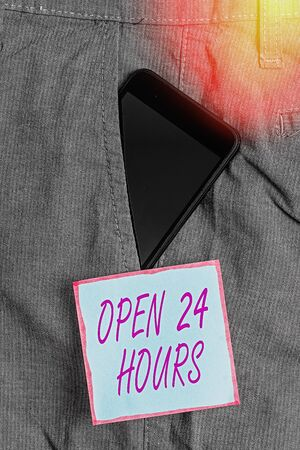 Word writing text Open 24 Hours. Business photo showcasing available all day and all night without closing or stopping Smartphone device inside formal work trousers front pocket near note paper