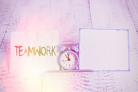 Conceptual hand writing showing Teamwork. Concept meaning combined action of group especially when effective and efficient Alarm clock tilted above buffer wire in front of notepaper