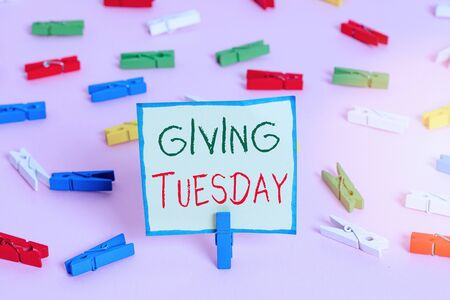 Text sign showing Giving Tuesday. Business photo text international day of charitable giving Hashtag activism Colored clothespin papers empty reminder pink floor background office pin