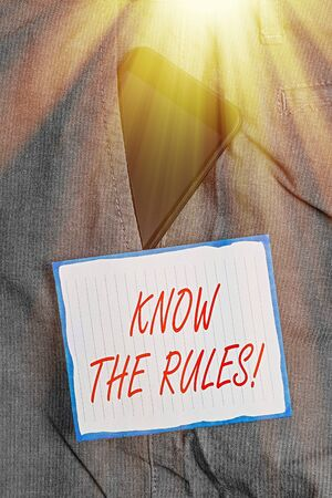 Conceptual hand writing showing Know The Rules. Concept meaning set explicit or regulation principles governing conduct Smartphone device inside trousers front pocket note paper Stock Photo