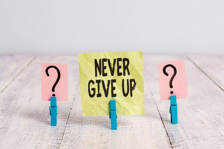 Text sign showing Never Give Up. Business photo text be persistent to keep on trying to improve the condition Scribbled and crumbling sheet with paper clips placed on the wooden table