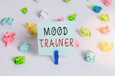 Text sign showing Mood Trainer. Business photo showcasing a demonstrating who trains to alleviate mood disorders Colored crumpled papers empty reminder white floor background clothespin