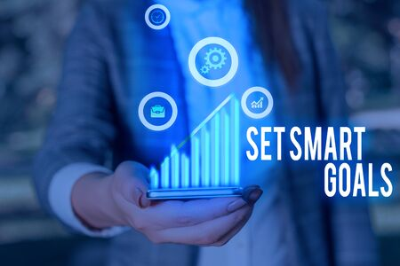 Writing note showing Set Smart Goals. Business concept for giving criteria to guide in the setting of objectives Stock Photo