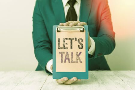 Conceptual hand writing showing Lets Is Talk. Concept meaning suggesting in the beginning of a conversation on the topic Man holds empty paper with copy space in front of him Space Stock Photo