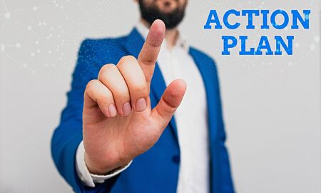 Writing note showing Action Plan. Business concept for detailed plan outlining actions needed to reach goals or vision Businessman with pointing finger in front of him
