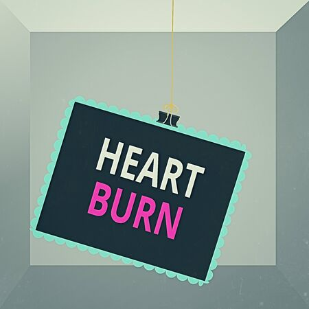 Conceptual hand writing showing Heart Burn. Concept meaning a burning sensation or pain in the throat from acid reflux Stamp stuck binder clip square color frame rounded tip