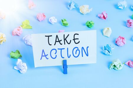 Handwriting text writing Take Action. Conceptual photo to do something or act in order to get a particular result Colored crumpled papers empty reminder blue floor background clothespin