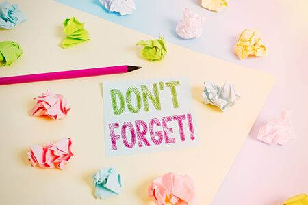 Text sign showing Don T Forget. Business photo showcasing used to remind someone about an important fact or detail Colored crumpled papers empty reminder blue yellow background clothespin