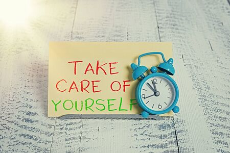 Word writing text Take Care Of Yourself. Business photo showcasing a polite way of ending a gettogether or conversation Mini blue alarm clock stand tilted above buffer wire in front of notepaper Banque d'images