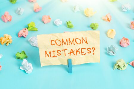 Word writing text Common Mistakes Question. Business photo showcasing repeat act or judgement misguided making something wrong Colored crumpled papers empty reminder blue floor background clothespin