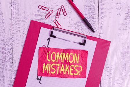 Text sign showing Common Mistakes Question. Business photo showcasing repeat act or judgement misguided making something wrong Clipboard paper sheet clips ballpoint crushed note old vintage background 版權商用圖片