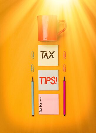 Handwriting text writing Tax Tips. Conceptual photo compulsory contribution to state revenue levied by government Coffee cup blank colored sticky note two ballpoints clips yolk background