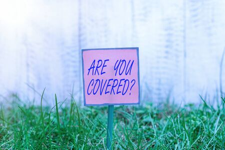 Text sign showing Are You Covered Question. Business photo text asking showing if they had insurance in work or life Plain empty paper attached to a stick and placed in the green grassy land