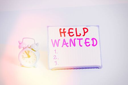 Writing note showing Help Wanted. Business concept for An ad in the paper an employer places to find a new employee Alarm clock beside a Paper sheet placed on pastel backdrop