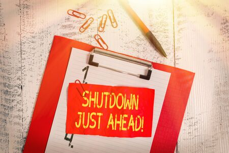 Text sign showing Shutdown Just Ahead. Business photo showcasing closing factory business either short time or forever Clipboard paper sheet clips ballpoint crushed note old vintage background Banque d'images