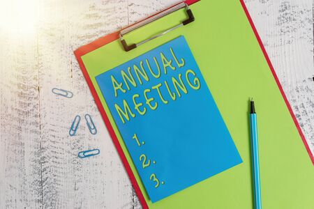 Conceptual hand writing showing Annual Meeting. Concept meaning yearly meeting of the general membership of an organization Colored clipboard paper marker sticky note wooden background