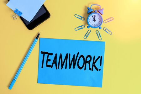 Text sign showing Teamwork. Business photo showcasing combined action of group especially when effective and efficient Smartphone clock clips paper sheet notepad ballpoint colored background