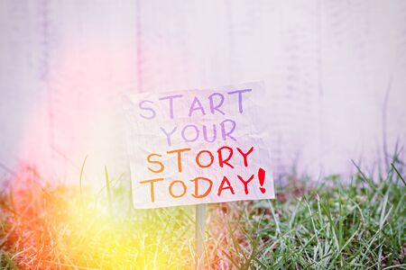 Conceptual hand writing showing Start Your Story Today. Concept meaning work hard on yourself and begin from this moment Plain paper attached to stick and placed in the grassy land