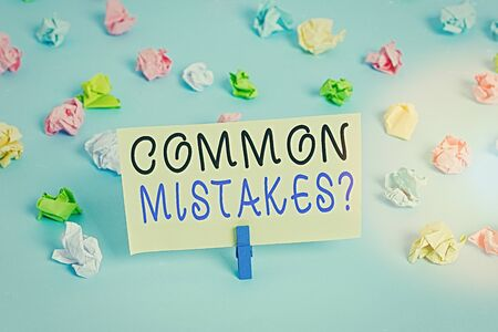 Handwriting text writing Common Mistakes question. Conceptual photo repeat act or judgement misguided or wrong Colored crumpled papers empty reminder blue floor background clothespin 版權商用圖片