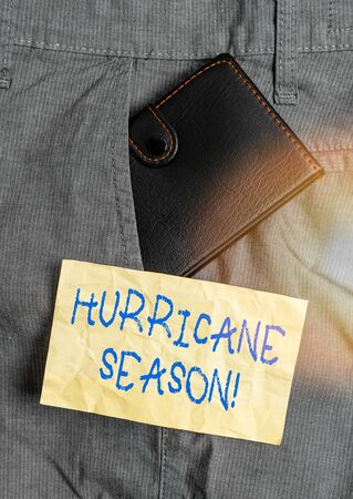 Word writing text Hurricane Season. Business photo showcasing time when most tropical cyclones are expected to develop Small little wallet inside man trousers front pocket near notation paper