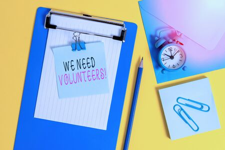 Word writing text We Need Volunteers. Business photo showcasing someone who does work without being paid for it Clipboard sheet note binder pencil clips clock envelop colored background Banco de Imagens
