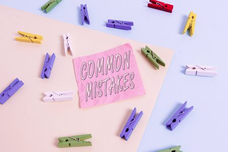 Text sign showing Common Mistakes. Business photo text actions that are often used interchangeably with error Colored clothespin paper empty reminder yellow blue floor background office