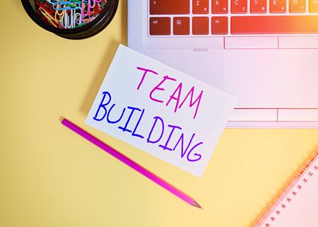 Word writing text Team Building. Business photo showcasing various types of activities used to enhance social relations Laptop pencil squared paper sheet clips container spiral colored background