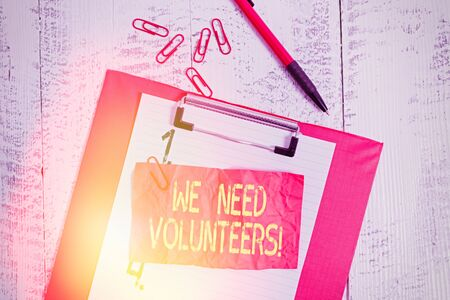 Text sign showing We Need Volunteers. Business photo showcasing someone who does work without being paid for it Clipboard paper sheet clips ballpoint crushed note old vintage background