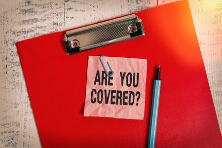 Conceptual hand writing showing Are You Covered Question. Concept meaning asking showing if they had insurance in work or life Colored clipboard crushed sticky note marker old wooden background